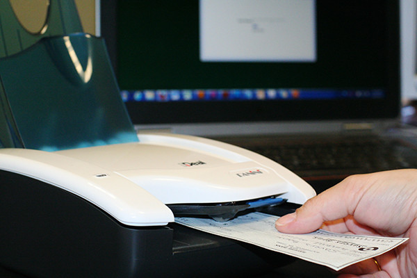 Person using Remote Deposit by inserting a check and converting it from paper to an electronic image.