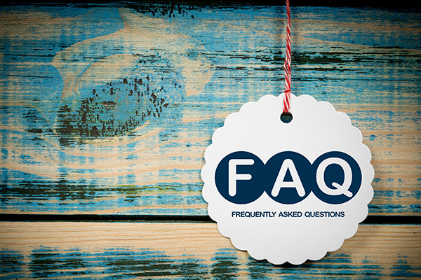 Circular FAQ tag hanging by a string against blue stained wood